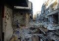Местный житель на улице среди разрушенных зданий в районе Дахания в Дамаске
