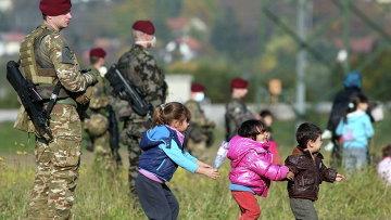 Дети беженцев играют рядом со словенскими военными на хорватско-словенской границе