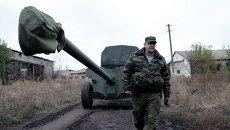 Военнослужащий у военной техники, отведенной от линии соприкосновения ДНР, на специально подготовленной площадке в Донецкой области
