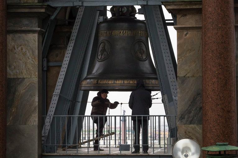 Мужчины звонят в колокол во время поминальной службы по жертвам авиакатастрофы А321 в Исаакиевском соборе