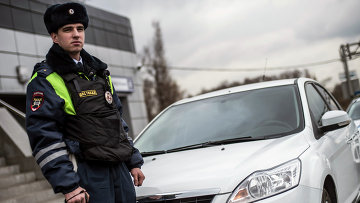Сотрудник ГИБДД рядом с автомобилем без специальных знаков и проблескового маячка во время рейда скрытых патрулей ДПС в Москве. Архивное фото