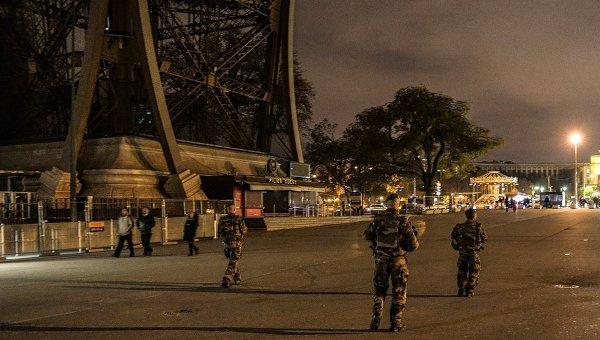 Французские военнослужащие у Эйфелевой башни, на которой отключили подсветку в память о жертвах крупнейшего в истории Франции террористического акта, произошедшего 13 ноября 2015 года в Париже