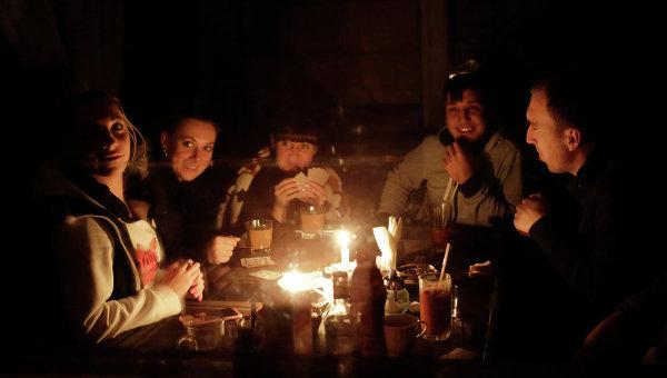 Люди сидят при свечах на кухне в своем доме