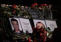 Портреты погибших в Сирии подполковника Олега Пешкова и матроса Александра Позынича и цветы у памятника героям фильма Офицеры