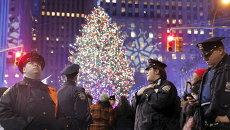 Офицеры полиции Нью-Йорка во время церемонии зажжения огней главной рождественской елки у небоскреба Рокфеллер-центра в Нью-Йорке, США