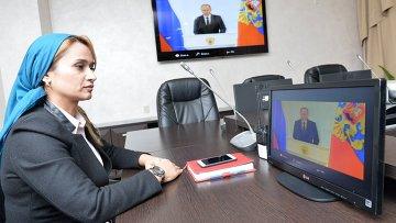 Сотрудница МЧС России по Чеченской Республике смотрит телевизионную трансляцию послания президента РФ Владимира Путина к Федеральному Собранию