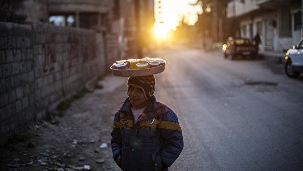 Подросток продает напитки на одной из улиц в городе Камышли провинции Эль-Хасаке на северо-востоке Сирии, находящемся под контролем ассирийских сил самообороны Соторо