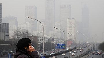 Жительница Пекина одевает маску на лицо, чтобы защититься от смога. 20 декабря 2015