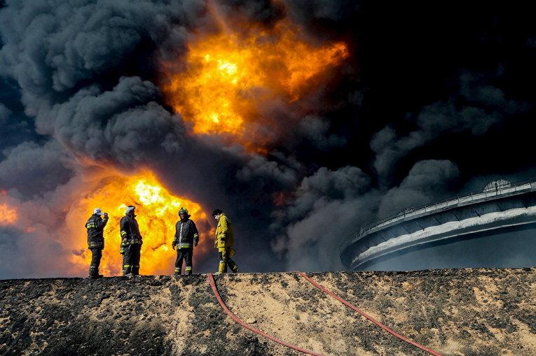Пожарные возле нефтяного резервуара в городе Эс-Сидер, Ливия