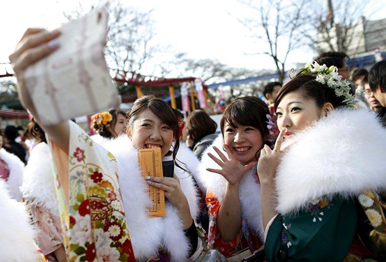 Японские девушки во время торжественной церемонии дня совершеннолетия в парке развлечений в Токио
