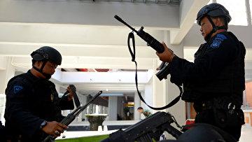 Сотрудники правоохранительных органов Индонезии проверяют оружие перед выходом на службу. 15 января 2016