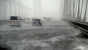 Автомобили едут по вантовому мосту через бухту Золотой Рог во время снежного циклона во Владивостоке. Архивное фото