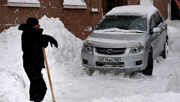 Мужчина убирает снег на улице Пушкинская во Владивостоке. Архивное фото