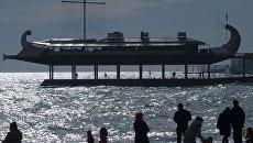 Отдыхающие гуляют вечером по пляжу у одного из ресторанов в виде галеры на набережной Ялты. Архивное фото
