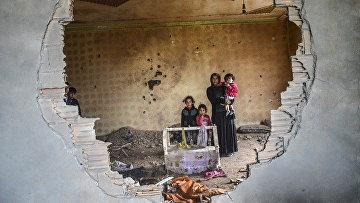 Женщина и дети в разрушенном доме в Курдском городе Силопи на юго-востоке Турции, недалеко от границы с Ираком, январь 2016 год