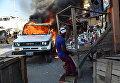 Горящий автомобиль на улице в Порт-о-Пренсе во время протестов, Гаити