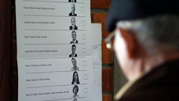 Мужчина изучает бюллетень для голосования на избирательном участке в городе Оэйраш, Португалия. 24 января 2016