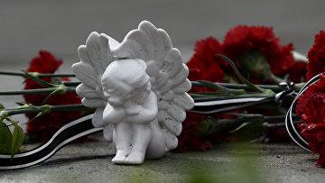 Цветы и фигурка ангела в память о погибших в пожаре в Доме профсоюзов