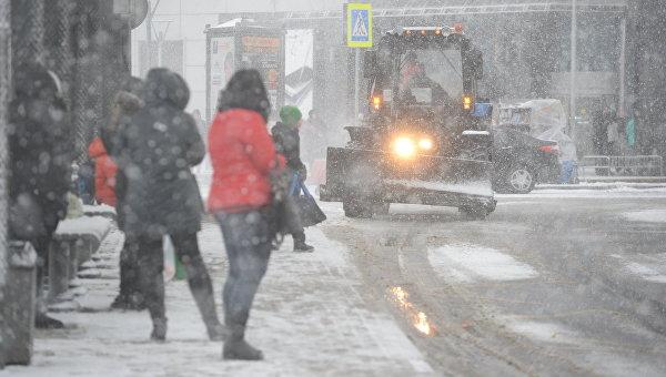 Люди во время снегопада стоят на остановке общественного транспорта в районе станции метро Щукинская в Москве. Архивное фото