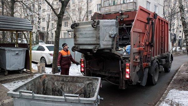 Сотрудник коммунальных служб выгружает мусор из контейнера в мусоровоз. Архивное фото