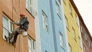 Маляр-верхолаз на стене жилого домов в центре города. Архивное фото