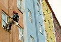 Маляр-верхолаз на стене жилого домов в центре города