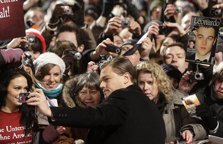 Американский актер и продюсер Леонардо Ди Каприо фотографируется с поклонниками во время кинофестиваля в Берлине. Февраль 2010