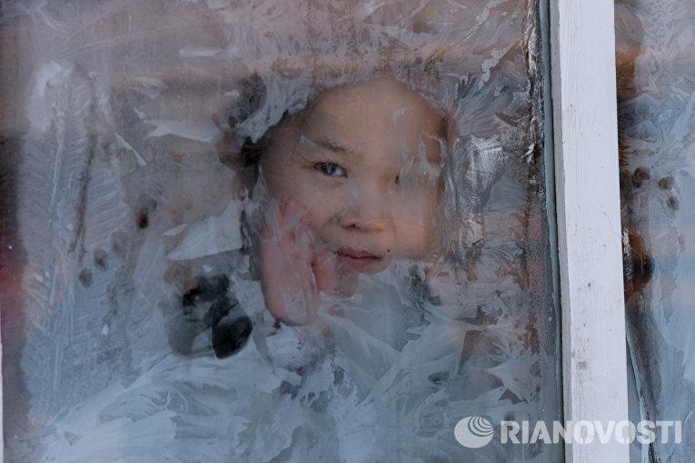 Девочка в окне домика на зимней чабанской стоянке в местечке Чумур-Ой Тес-Хемского кожууна Республики Тыва