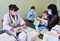 Врач проводит осмотр ребенка в детской поликлинике №3 города Челябинска в период сезонного роста заболеваемости гриппом и ОРВИ.