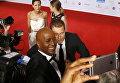 Актер Тиль Швайгер и телеведущий Яред Дибаба делают селфи на церемонии вручения премии Золотая камера в Гамбурге, Германия