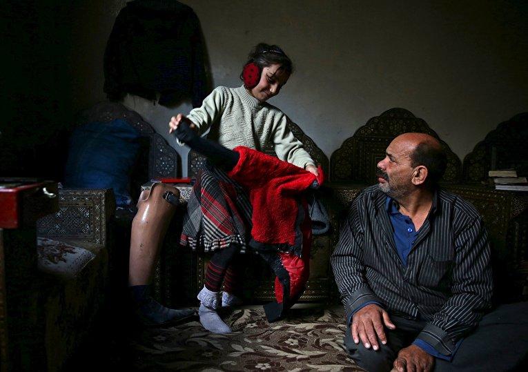Инвалид Шахрур с дочерью у себя дома, Ирбин, Сирия