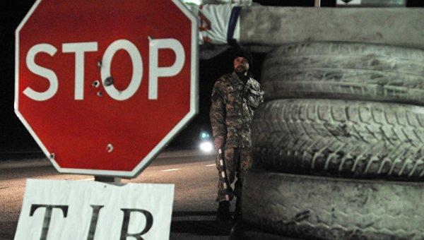 Украинский активист стоит на блокпосту возле Львова, блокируя движение грузовиков с российскими номерами во Львовской области