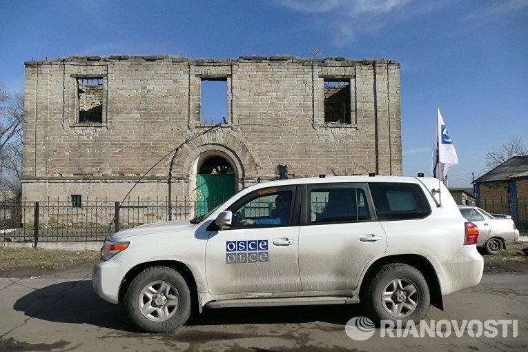 Автомобиль ОБСЕ у разрушенного дома в поселке Зайцево в Донецкой области