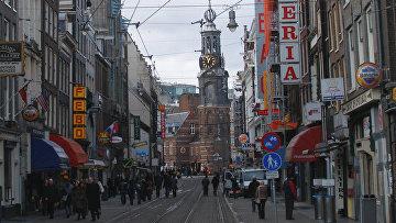 Оживленная улица ведет к башне Монетного двора. Амстердам