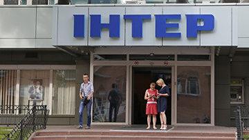 Люди у входа в здание телеканала Интер в Киеве, Украина