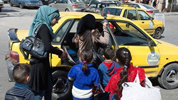 Женщины с детьми садятся в такси на одной из улиц Дамаска в первый день перемирия