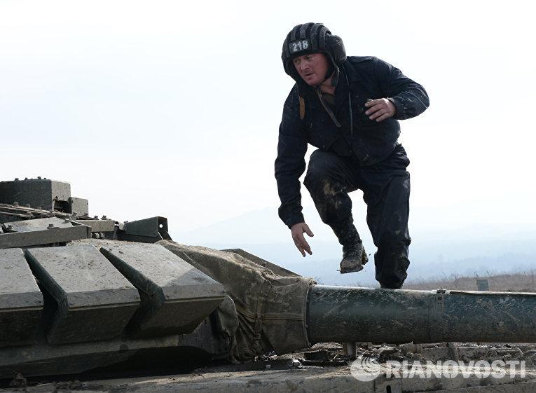 Военнослужащий на броне танка Т-72Б3 17-й отдельной мотострелковой бригады 58-й армии на огневом рубеже во время соревнований по танковому биатлону