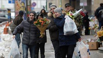 Мужчины с букетами цветов в преддверии праздника 8 марта в Москве