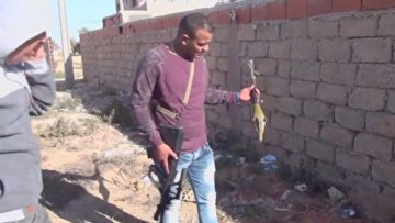 Сотрудники полиции держат гранатомет, найденный на месте нападения боевиков ИГИЛ на город Бен-Гардан, Тунис