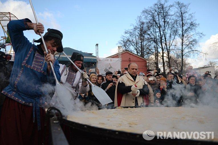 Участники масленичных гуляний во время установления рекорда по приготовлению самого большого блина России в саду Эрмитаж в Москве