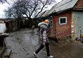 Девушка во дворе своего дома в поселке Зайцево под Горловкой, который был обстрелян украинскими силовиками