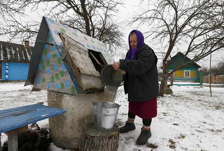 Женщина набирает воду из колодца в Белоруссии