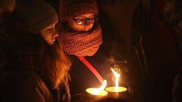 Участники акции на стрелке Васильевского острова в Санкт-Петербурге зажигают свечи в память о погибших в авиакатастрофе Boeing-737-800 в Ростове-на-Дону