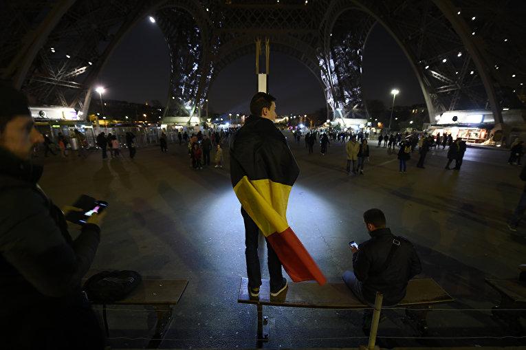 Люди возле Эйфелевой башни окрашенной в цвета бельгийского флага в память о жертвах терактов. Париж, Франция