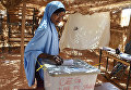 Женщина бросает бюллетень во время президентских выборов на избирательном участке в Ниамей, Нигера