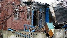 Мужчина у дома, поврежденного в результате обстрела украинскими силовиками. Архивное фото