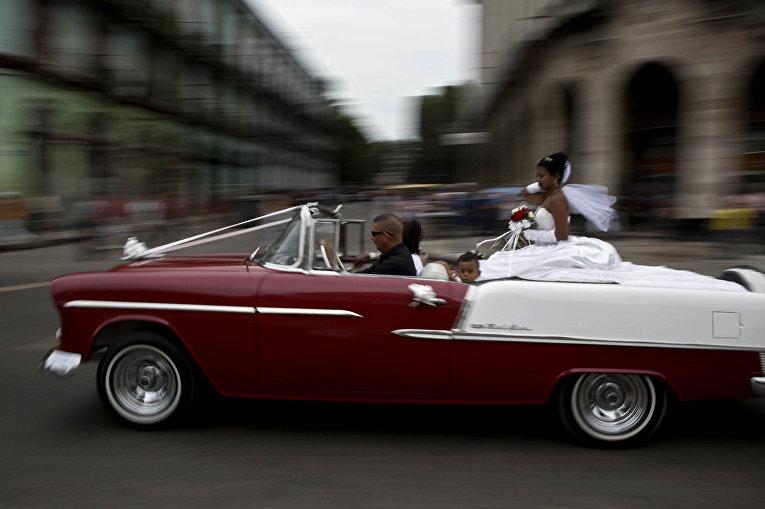 Американский классический автомобиль везет невесту на церемонию бракосочетания в Гаване, Куба
