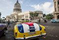 Классический американский автомобиль с изображением кубинского флага возле здания Капитолия в Гаване, Куба