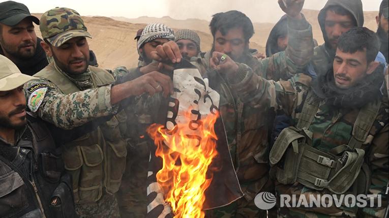 Сирийские солдаты сжигают флаг террористической группировки Исламское государство (запрещенная в РФ), снятый с крепости Пальмиры