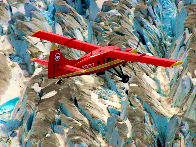 Самолет пролетает над горными ледниками Аляски